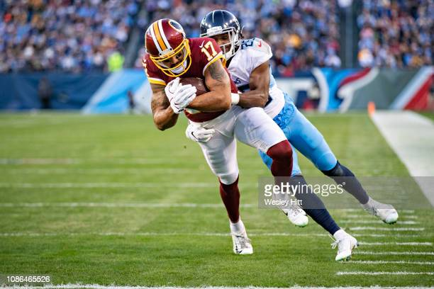 Michael Floyd of the Washington Redskins runs a pass in for a touchdown while being grabbed by Adoree Jackson of the Tennessee Titans at Nissan...