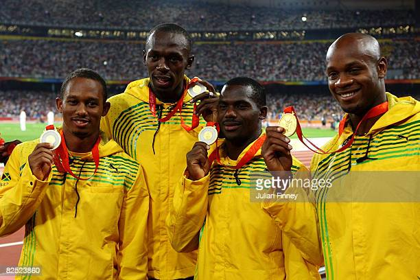 Michael Frater Usain Bolt Nesta Carter and Asafa Powell of Jamaica receive their gold medals during the medal ceremony for the Men's 4 x 100m Relay...