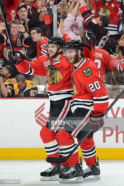 Michael Frolik and Brandon Saad of the Chicago Blackhawks celebrate a Hawks goal in Game One of the Stanley Cup Final against the Boston Bruins at...