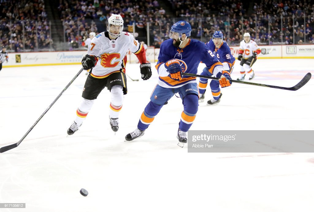 Michael Frolik #67 of the Calgary Flames chases the puck against Nick Leddy #2 of the New York Islanders in the second period during their game at Barclays Center on February 11, 2018 in the Brooklyn borough of New York City.