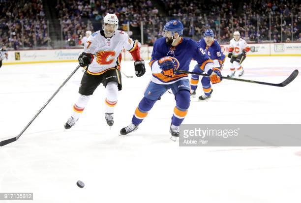 Michael Frolik of the Calgary Flames chases the puck against Nick Leddy of the New York Islanders in the second period during their game at Barclays...