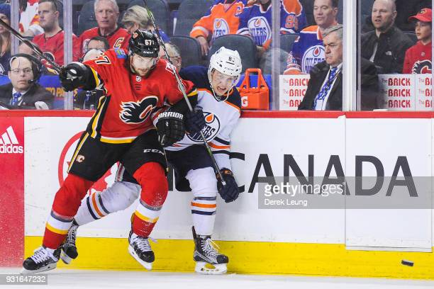 Michael Frolik of the Calgary Flames fights Matthew Benning of the Edmonton Oilers for the puck during an NHL game at Scotiabank Saddledome on March...