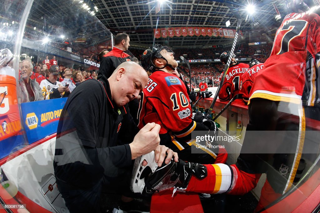 Michael Frolik #67 of the Calgary Flames gets his skate fixed during an NHL game against the Pittsburgh Penguins on March 13, 2017 at the Scotiabank Saddledome in Calgary, Alberta, Canada.