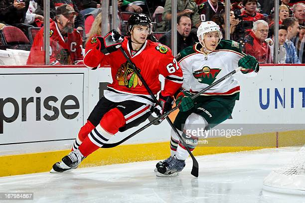 Michael Frolik of the Chicago Blackhawks and Jared Spurgeon of the Minnesota Wild skate around the boards in Game Two of the Western Conference...
