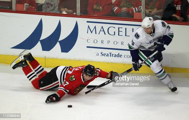 Michael Frolik of the Chicago Blackhawks moves the puck forward with his hand while holding the stick of Mikael Samuelsson of the Vancouver Canucks...