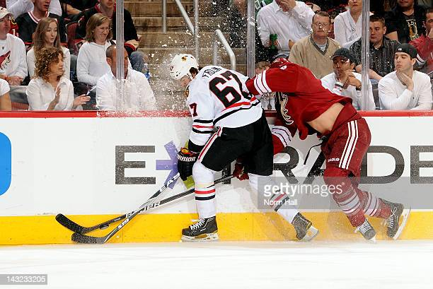 Michael Frolik of the Chicago Blackhawks tries to keep conrtol of the puck along the boards while fighting off Rostislav Klesla of the Phoenix...