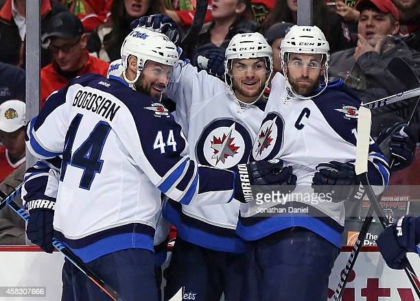 Michael Frolik of the Winnipeg Jets celebrates his first period goal with Zach Bogosian and Andrew Ladd against the Chicago Blackhawks at the United...