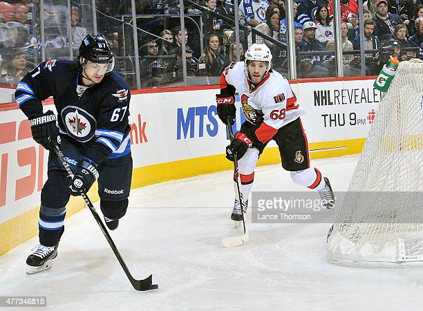 Michael Frolik of the Winnipeg Jets plays the puck around the net as Mike Hoffman of the Ottawa Senators gives chase during third period action at...