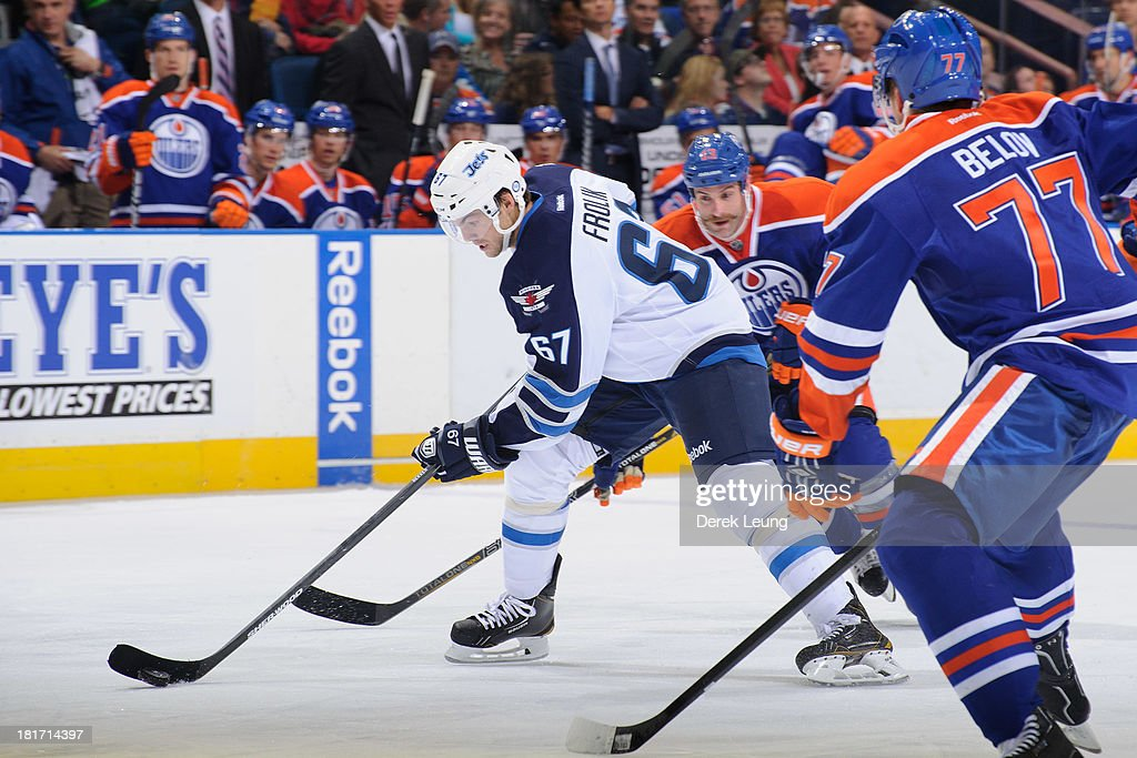 Michael Frolik #67 of the Winnipeg Jets splits the defence of Anton Belov #77 and Mike Brown #13 of the Edmonton Oilers during a preseason NHL game at Rexall Place on September 23, 2013 in Edmonton, Alberta, Canada.