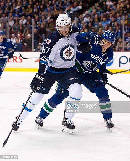 Michael Froliks of the Winnipeg Jets and Kevin Bieksa of the Vancouver Canucks battle for position while chasing a loose puck during the first period...