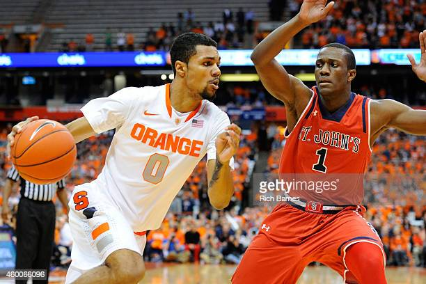 Michael Gbinije of the Syracuse Orange drives to the basket against defender Phil Greene IV of the St John's Red Storm during the first half of the...