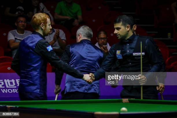 Michael Georgiou of Cyprus shakes hands with Anthony McGill of Scotland during the group match between Scotland and Cyprus on day 2 of 2017 Snooker...