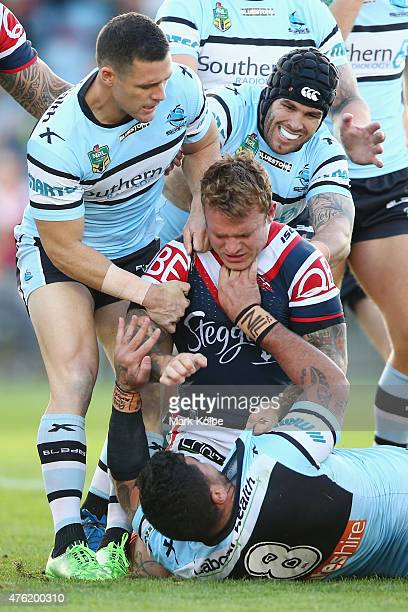 Michael Gordon and Michael Ennis of the Sharks pull away Jake Friend of the Roosters as he scuffles with Andrew Fifita of the Sharks during the round...
