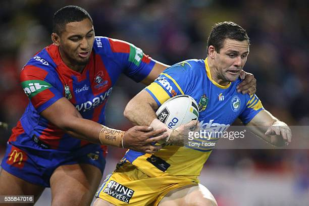 Michael Gordon of the Eels is tackled by Pauli Pauli of the Knights during the round 12 NRL match between the Newcastle Knights and the Parramatta...