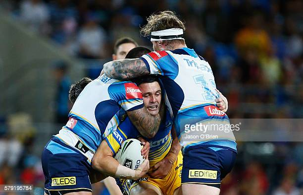 Michael Gordon of the Eels is tackled by the Titans defence during the round 20 NRL match between the Gold Coast Titans and the Parramatta Eels at...