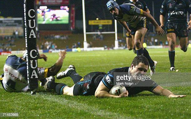 Michael Gordon of the Panthers beats the defence of Ty Williams of the Cowboys to score during the round 19 NRL match between the Penrith Panthers...
