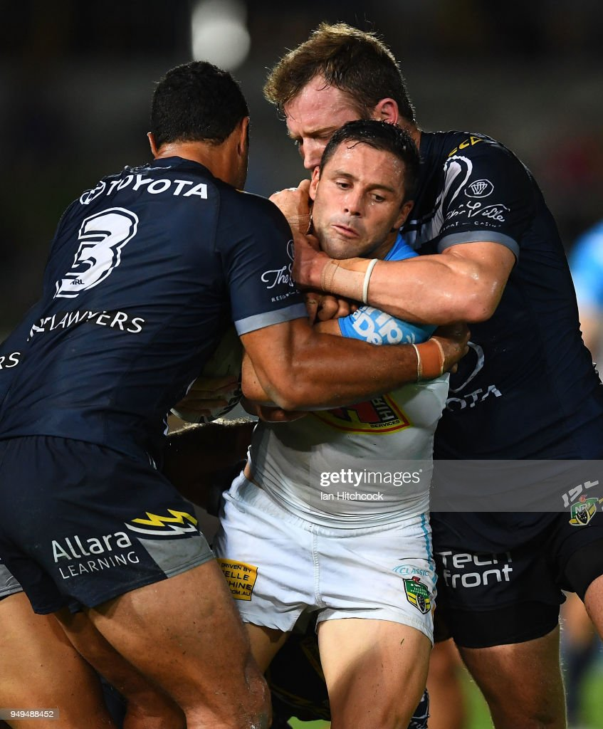 Michael Gordon of the Titans is tackled by Justin O'Neil and Gavin Cooper of the Cowboys during the round seven NRL match between the North Queensland Cowboys and the Gold Coast Titans at 1300SMILES Stadium on April 21, 2018 in Townsville, Australia.