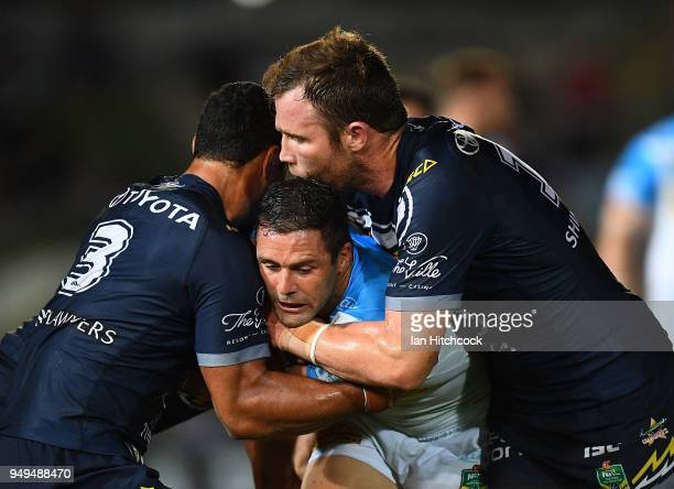 Michael Gordon of the Titans is tackled by Justin O'Neil and Gavin Cooper of the Cowboys during the round seven NRL match between the North...