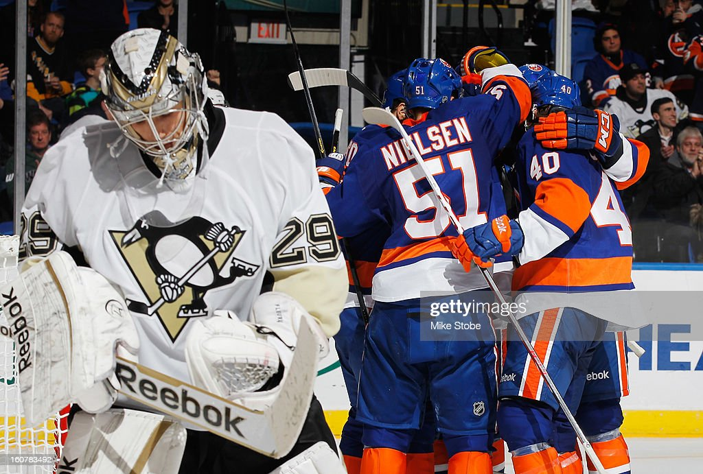 Michael Grabner #40 of the New York Islanders is mobbed by teammates congratulating him on his third period goal as goaltender Marc-Andre Fleury #29 of the Pittsburgh Penguins looks away at Nassau Veterans Memorial Coliseum on February 5, 2013 in Uniondale, New York.