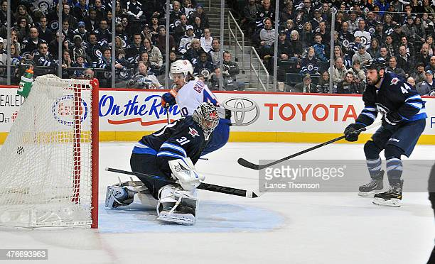 Michael Grabner of the New York Islanders watches as the puck flies into the net behind goaltender Ondrej Pavelec of the Winnipeg Jets for the...