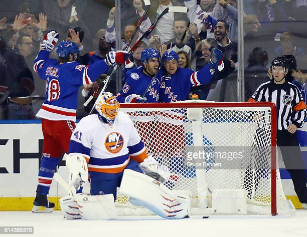 Michael Grabner of the New York Rangers celebrates his first period goal against Jaroslav Halak of the New York Islanders and is joined by Marc Staal...