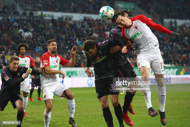 Michael Gregoritsch of Augsburg battles for the ball with Christian Guenter of Freiburg during the Bundesliga match between FC Augsburg and SportClub...