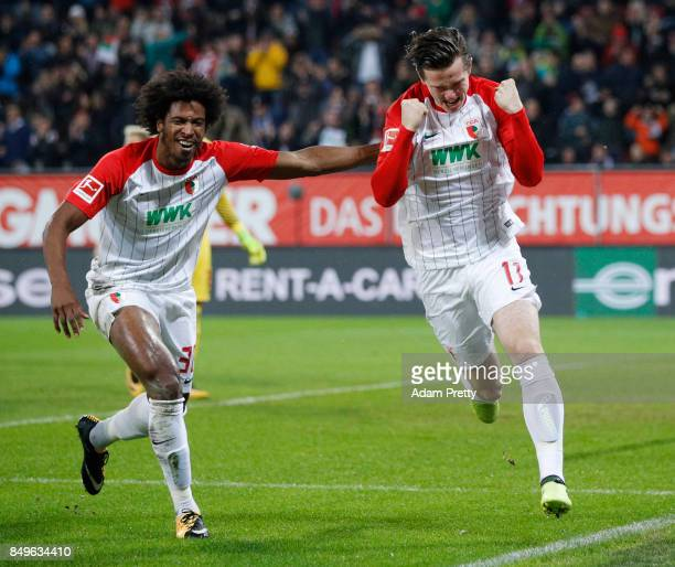 Michael Gregoritsch of Augsburg celebrates after he scored his teams first goal to make it 10 with Caiuby of Augsburg during the Bundesliga match...