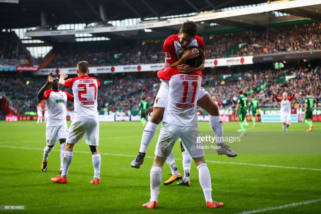 Michael Gregoritsch #11 of Augsburg celebrates with Rani Khedira after scoring his team's first goal to make it 0-1 during the Bundesliga match between SV Werder Bremen and FC Augsburg at Weserstadion on October 29, 2017 in Bremen, Germany.