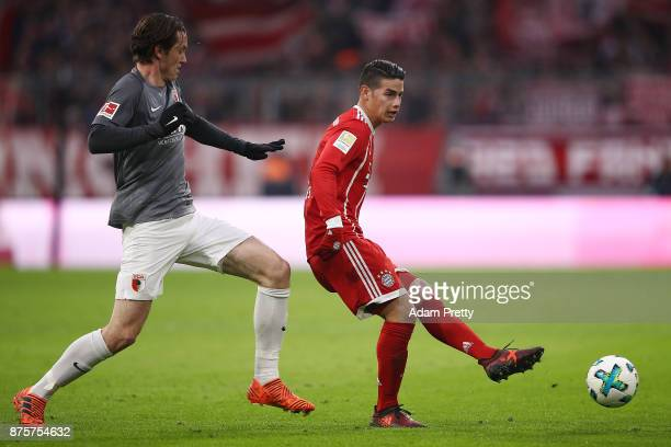 Michael Gregoritsch of Augsburg chases James Rodriguez of Bayern Muenchen during the Bundesliga match between FC Bayern Muenchen and FC Augsburg at...