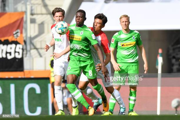 Michael Gregoritsch of Augsburg Denis Zakaria of Moenchengladbach JaCheol Koo of Augsburg and Oscar Wendt of Moenchengladbach during the Bundesliga...