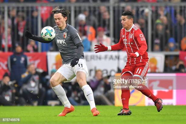 Michael Gregoritsch of Augsburg fights for the ball with James Rodriguez of Bayern Muenchen during the Bundesliga match between FC Bayern Muenchen...