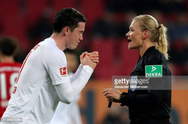Michael Gregoritsch of Augsburg talks to referee Bibiana Steinhaus during the Bundesliga match between FC Augsburg and FC Bayern Muenchen at WWKArena...