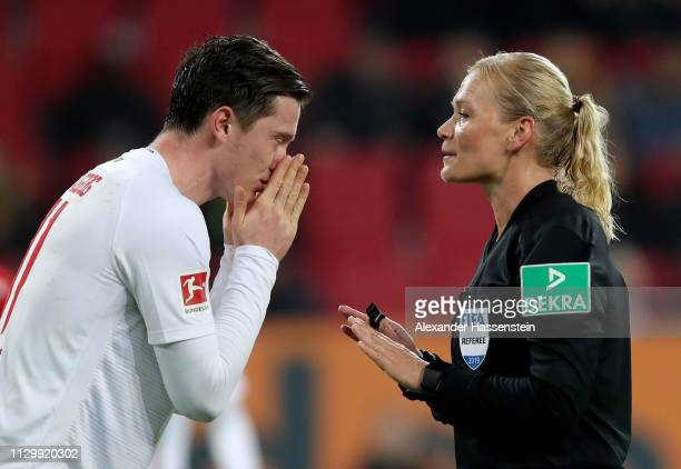 Michael Gregoritsch of Augsburg talks to referee Bibiana Steinhaus during the Bundesliga match between FC Augsburg and FC Bayern Muenchen at WWKArena...