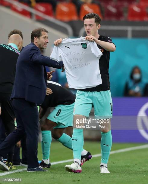 Michael Gregoritsch of Austria celebrates after scoring their side's second goal as he holds a t-shirt with a message of support for Christian...