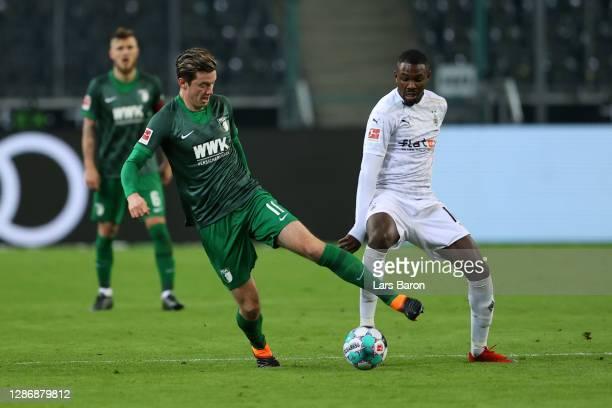 Michael Gregoritsch of FC Augsburg is challenged by Marcus Thuram of Borussia Monchengladbach during the Bundesliga match between Borussia...