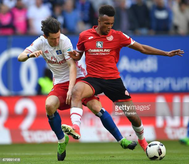 Michael Gregoritsch of Hamburg is challenged by Jean-Philippe Gbamin of Mainz during the Bundesliga match between Hamburger SV and 1. FSV Mainz 05 at...