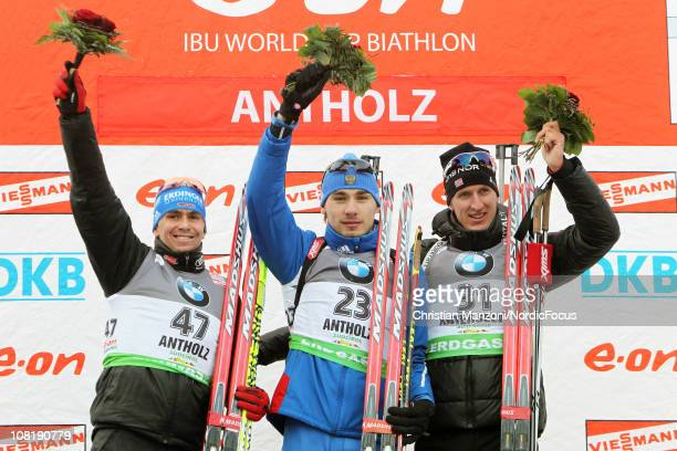 Michael Greis of Germany celebrates with Anton Shipulin of Russia and Lars Berger of Norway after the men's sprint during the EON IBU Biathlon World...