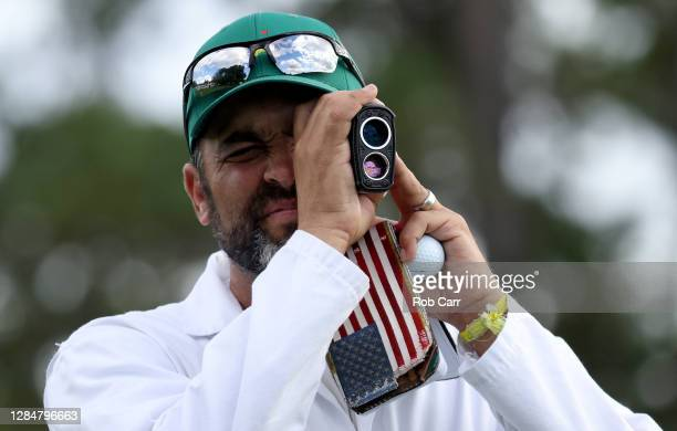 Michael Greller, caddie for Jordan Spieth of the United States, uses a range finder on the first tee during a practice round prior to the Masters at...