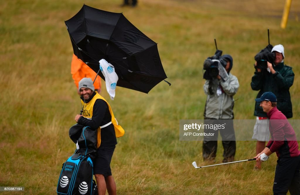 Michael Greller, US golfer Jordan Spieth's caddie battle with the wind on day two of the Open Golf Championship at Royal Birkdale golf course near Southport in north west England on July 21, 2017. / AFP PHOTO / Andy BUCHANAN / RESTRICTED
