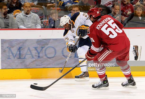 Michael Grier of the Buffalo Sabres makes a pass over the stick of Ed Jovanovski of the Phoenix Coyotes on January 8 2011 at Jobingcom Arena in...