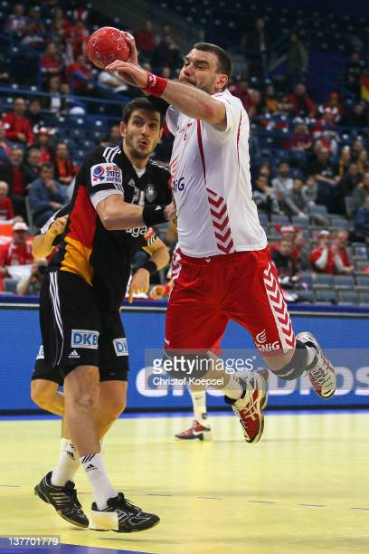 Michael Haass of Germany defends against Bartosz Jurecki of Poland during the Men's European Handball Championship second round group one match...