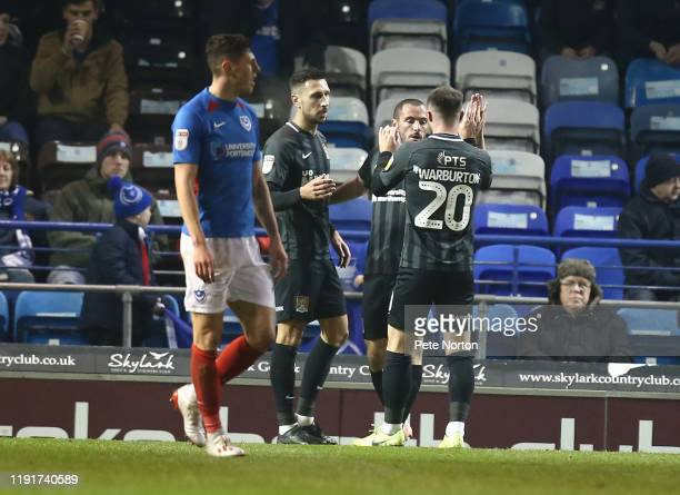 Michael Harriman of Northampton Town is congratulated by team mates after scoring his sides first goal during the Leasingcom Trophy match between...