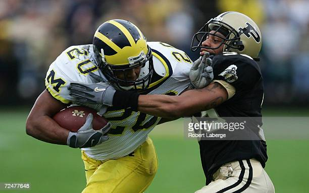 Michael Hart of the Michigan University Wolverines gets tackled by Brian Hickman of the Purdue University Boilermakers during the first half of the...