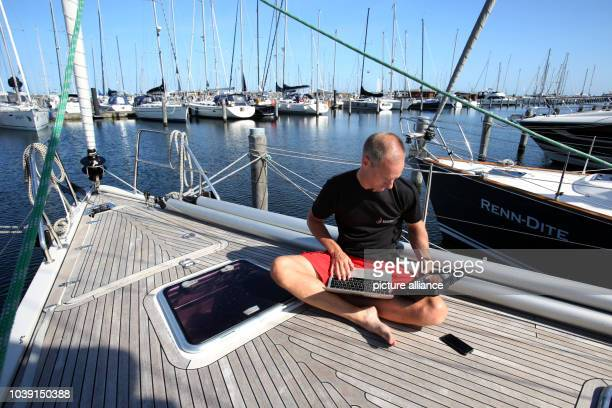 Michael Haufe general manager of Teamgeist GmbH in Heidsee sits with his computer on board a sailing boat at marina Hohe Duene in Warnemuende Germany...