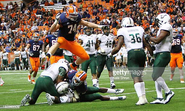 Michael Hay of the Syracuse Orange leaps over teammate Dorian Graham as he is tackled by Kayvon Webster of the South Florida Bulls during the game at...