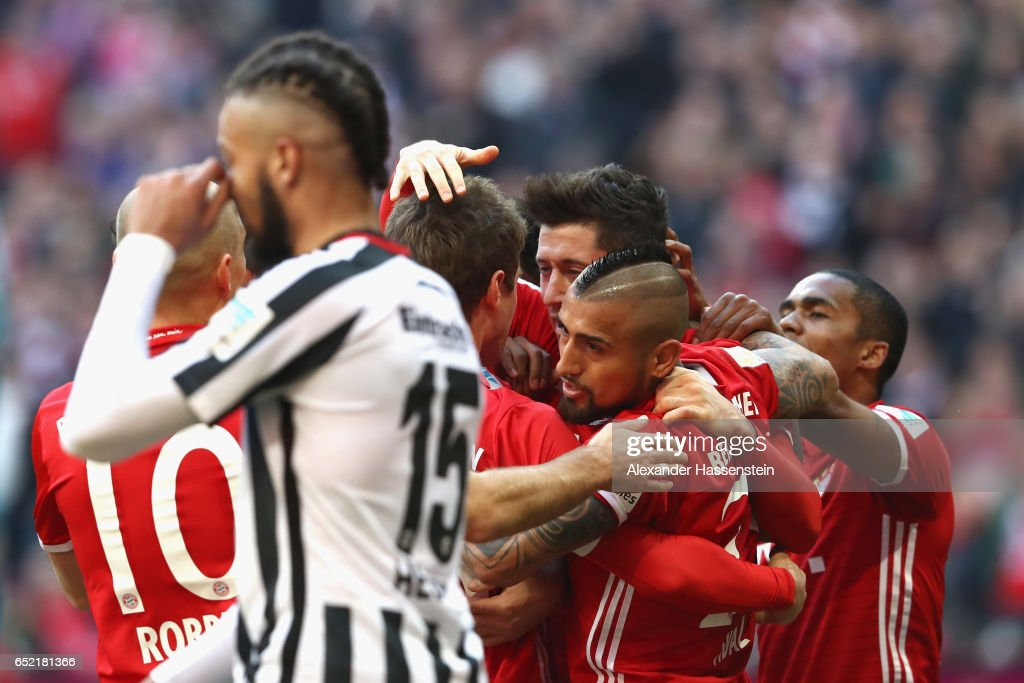 Michael Hector of Frankfurt reacts whilst Robert Lewandowski (C) of Muenchen celebrates his 1st team goal with his team mates during the Bundesliga match between Bayern Muenchen and Eintracht Frankfurt at Allianz Arena on March 11, 2017 in Munich, Germany.