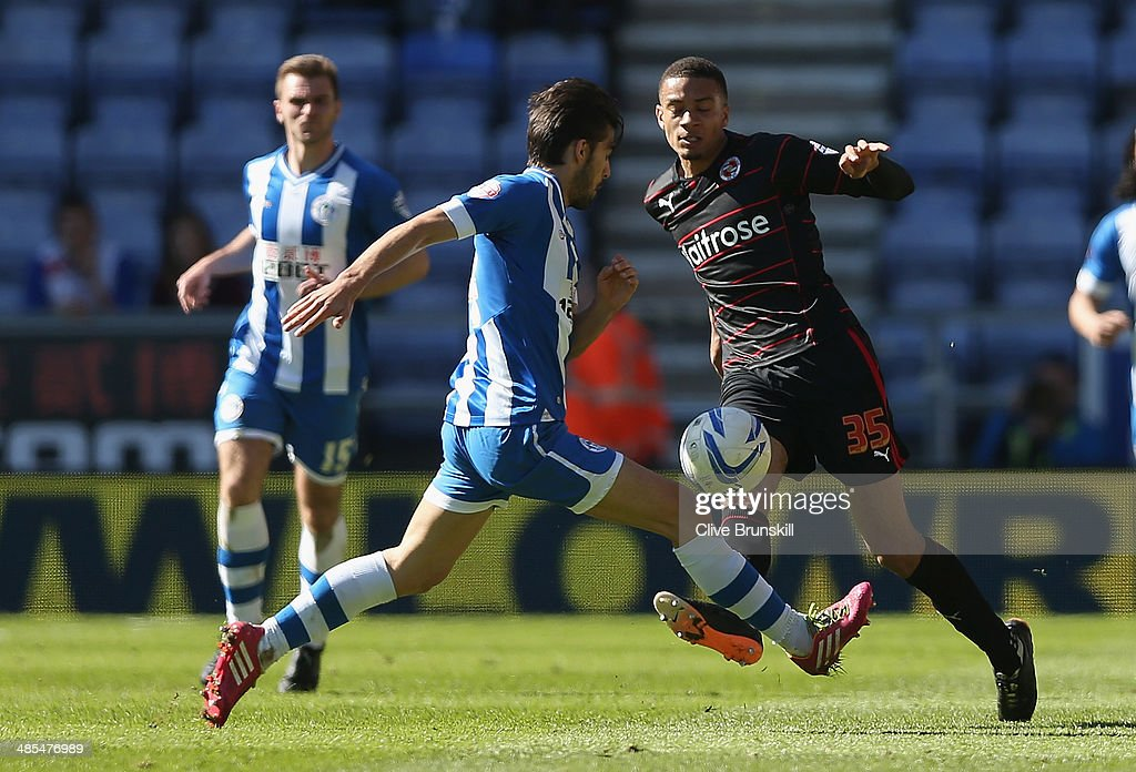 Michael Hector of Reading clears the ball from Jordi Gomez of Wigan Athletic during the Sky Bet Championship match between Wigan Athletic and Reading at DW Stadium on April 18, 2014 in Wigan, England.