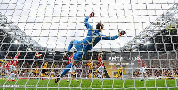 Michael Hefele of Dresden scores the second goal against goalie Daniel Bernhardt of Aalen during the Third League match between SG Dynamo Dresden and...