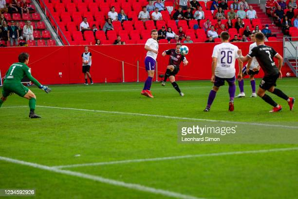Michael Heinloth of FC Ingolstadt 04 and players of Erzgebirge Aue in action during the DFB Cup first round match between FC Ingolstadt 04 and...