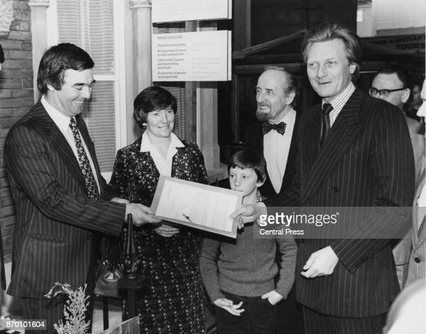 Michael Heseltine the Secretary of State for the Environment hands over the deeds to the GLC's 25000th home buyer schoolteacher Peter McCarthy his...